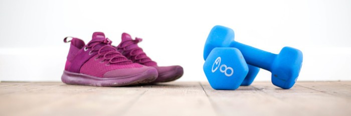 a pink pair of running shoes and blue dumbbells on a wooden gym floor
