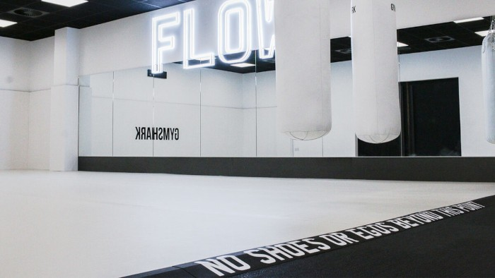 a bright white exercise room with mirrors and gymshark's logo