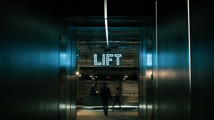 the entrance to gymshark lifting club with a neon lift sign