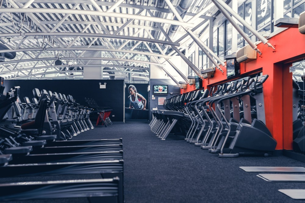a gym floor full of cardio equipment